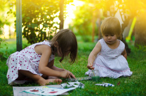 Girls having fun painting in the garden, together concept, famil