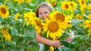 girl hugging sunflower